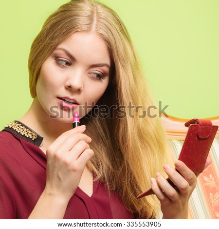 Young attractive woman applying pink lipstick on lips. Pretty gorgeous girl beautifying. Make up. - stock photo