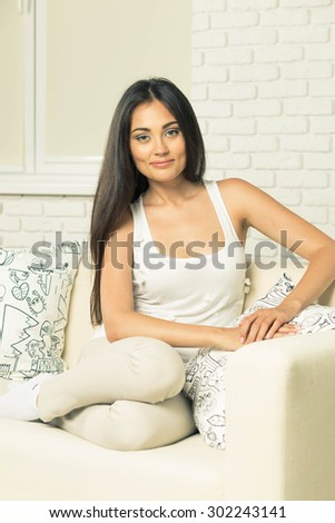 Young attractive woman at home sitting on couch