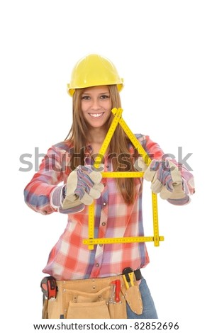 Young attractive woman builds a house from a yellow ruler - stock photo