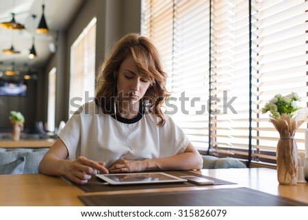 Young attractive woman concentrated reading electronic book on her digital tablet, caucasian female listening to music and browsing website pages on touch pad while sitting in modern coffee shop - stock photo