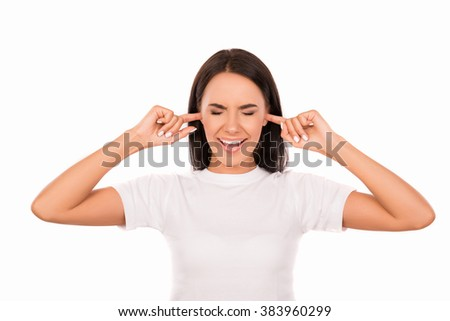 Young attractive woman covering her ears with fingers ignoring noise - stock photo