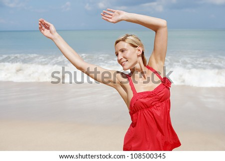 Young attractive woman dancing on a beach with the horizon and the sky in the background. - stock photo