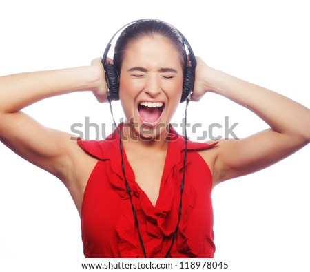 Young attractive woman dancing to music with headphones against white background - stock photo