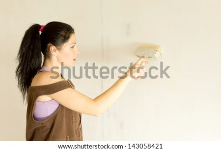 Young attractive woman decorating by painting walls.
