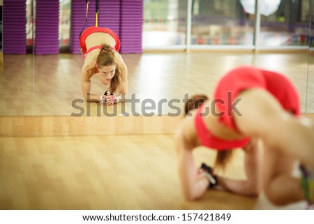 Young attractive woman does core abs crossfit training with trx fitness straps in the gym's studio, reflected in mirror - stock photo
