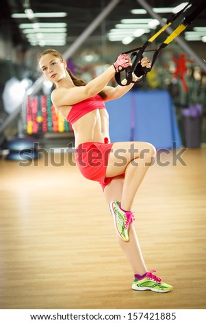 Young attractive woman does crossfit pull ups with fitness trx straps in the gym's studio - stock photo