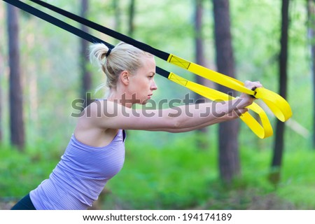 Young attractive woman does suspension training with fitness straps outdoors in the nature. - stock photo