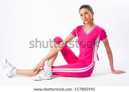 Young attractive woman doing exercise at white background - stock photo