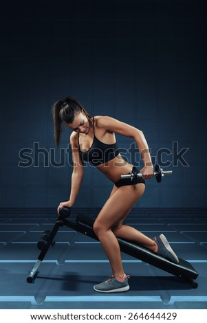 Young attractive woman doing exercises for the triceps - stock photo