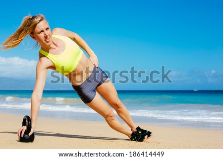 Young attractive woman doing kettle bell exercises outside. Fitness woman working out at the beach.  - stock photo