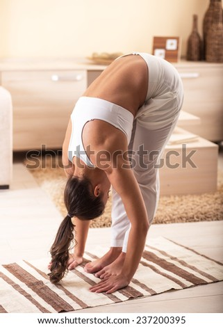 Young attractive woman doing yoga in her living room.Natural light ambient. - stock photo