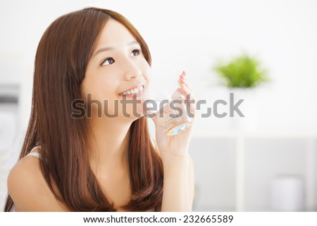 Young attractive woman drinking clean water - stock photo