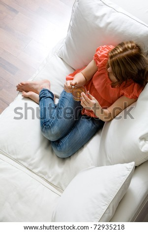 Young attractive woman drinking tea on sofa - stock photo