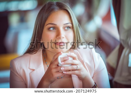 Young Attractive Woman Enjoying A Cup Of Coffee in Cafe - stock photo