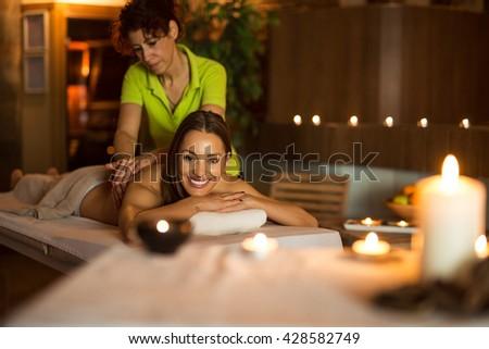 Young attractive woman enjoying back massage. - stock photo