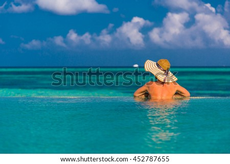 Young attractive woman enjoying the sun in the pool. Luxury travel background concept. - stock photo