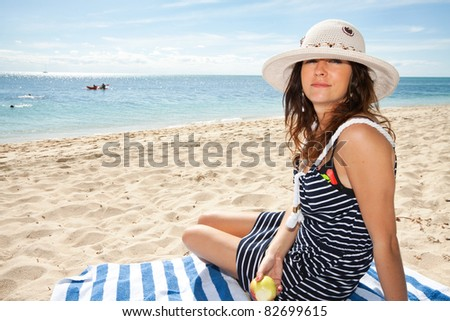 young attractive woman enjoys time on the beach - stock photo