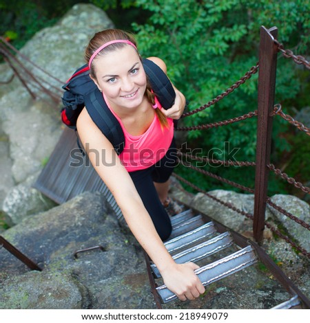Young attractive woman/female tourist climbing the ladder on the top of hill/mountain/rock (shallow DOF, colorful image) - stock photo