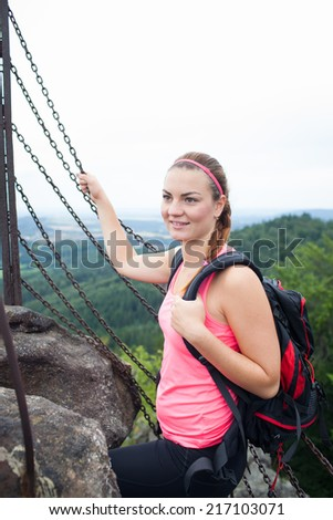 Young attractive woman/female tourist on the top of the hill/moutain/rock looking around on beautiful landscape - stock photo