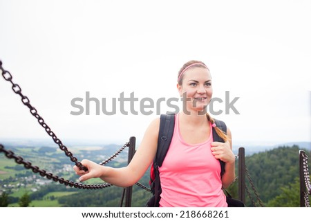 Young attractive woman/female tourist on the top of the hill/moutain/rock looking around on beautiful landscape (shallow DOF)