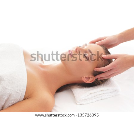 Young attractive woman getting massaging treatment over white background - stock photo