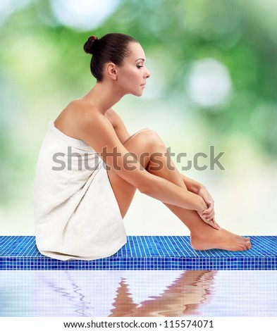 Young attractive woman getting spa on green background sitting by the pool