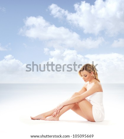 Young attractive woman getting spa treatment on the beach - stock photo
