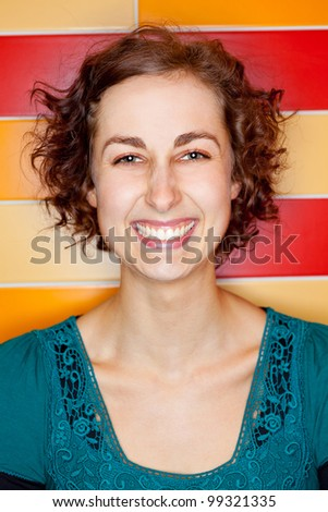 Young attractive woman grining with colorful tiles in the background - stock photo