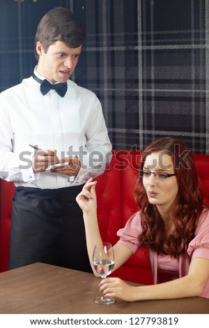 Young attractive woman having argue with waiter in a restaurant - stock photo