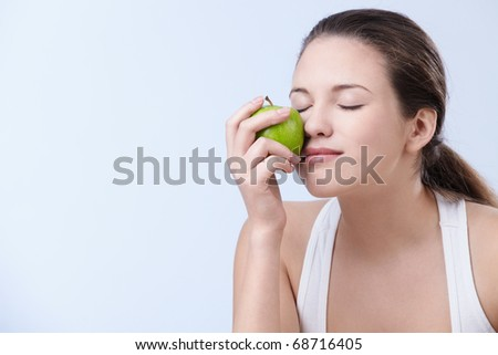 Young attractive woman holding an apple on a white background - stock photo