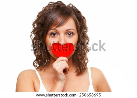 Young attractive woman holding red paper heart like a valentine card and hiding her face - stock photo