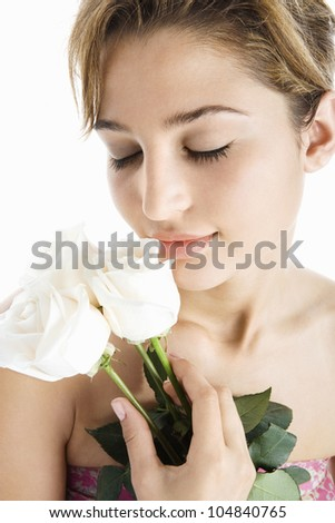 Young attractive woman holding three white roses next to her lips, smiling on a white background. - stock photo