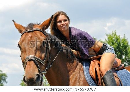 young attractive woman horseback riding in the summer sunny day - stock photo