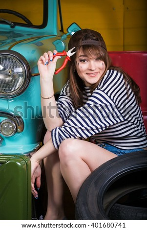 young attractive woman in a baseball cap sits in the garage near the retro car with tools. Girl holding pliers. - stock photo