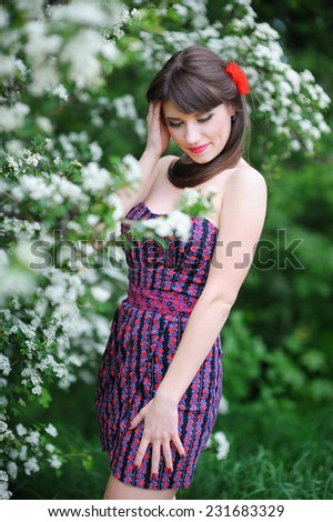 Young attractive woman in a green park on a summer day. - stock photo