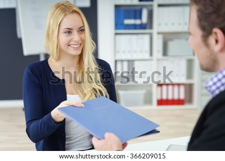 Young attractive woman in a job interview handing over a blue folder with her CV to a male business manager with a charming smile - stock photo