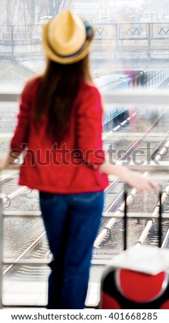 young attractive woman in a red coat and hat standing in the terminal or at the station with a suitcase. The girl met on a trip. she turned her back to the camera - stock photo