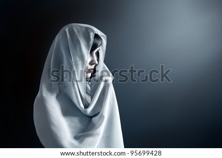 Young attractive woman in a veil prays on a dark background. - stock photo
