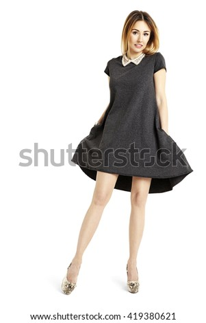 Young attractive woman in black dress posing and smiling to the camera.  - stock photo