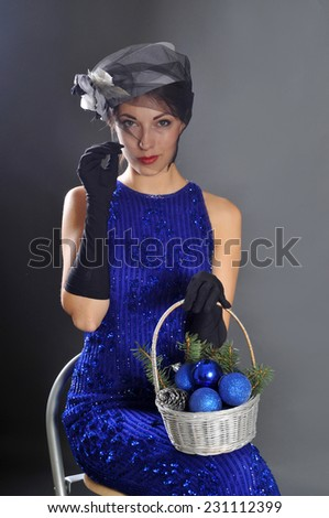 Young attractive woman in black hat and gloves with basket of balls - stock photo
