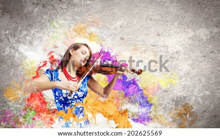 Young attractive woman in blue dress playing violin - stock photo