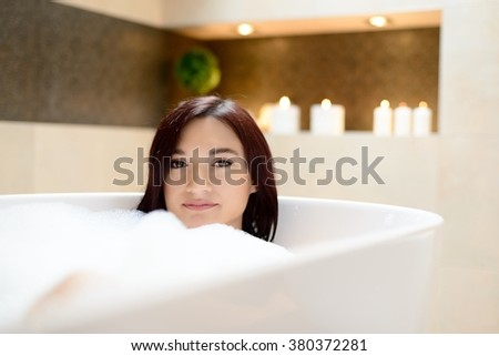 Young attractive woman in bubble bath. Relaxed. Woman in bathroom - stock photo