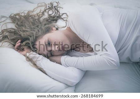 Young attractive woman in deep depression lying alone - stock photo