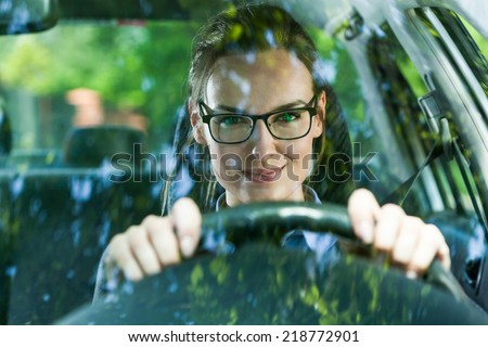 Young attractive woman in glasses driving a car - stock photo