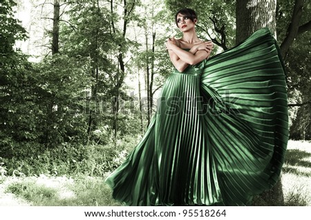 Young attractive woman in green long dress at forest - stock photo
