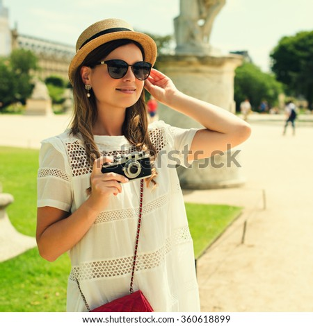 young attractive woman in hat, white dress, red bag and retro camera poses against Paris. Fashion and city style. Photo with instagram style filters - stock photo