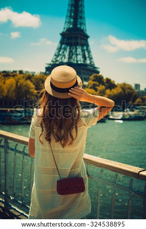 young attractive woman in hat, white dress, red bag poses in front of the Eiffel Tower in Paris - stock photo
