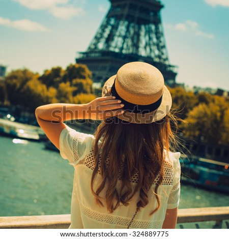 young attractive woman in hat, white dress, red bag poses in front of the Eiffel Tower in Paris. Photo with instagram style filters - stock photo