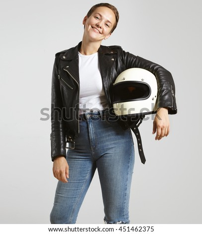 Young attractive woman in high waist jeans , leather motorbike jacket and blank white t-shirt with helmet in hand poses with smile looking at camera , isolated on white - stock photo