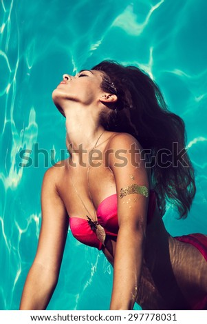 young attractive woman in  in pool with head thrown back above view